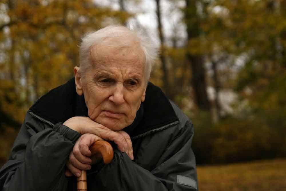 senior man resting head on cane