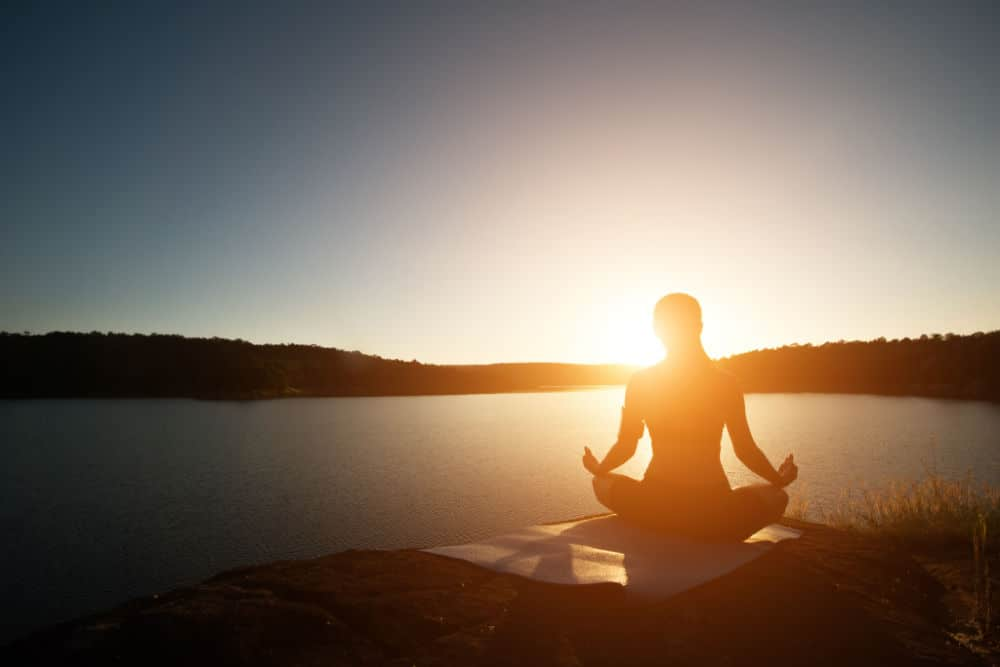 Silhouette of woman is practicing meditation at mountain lake during sunset.
