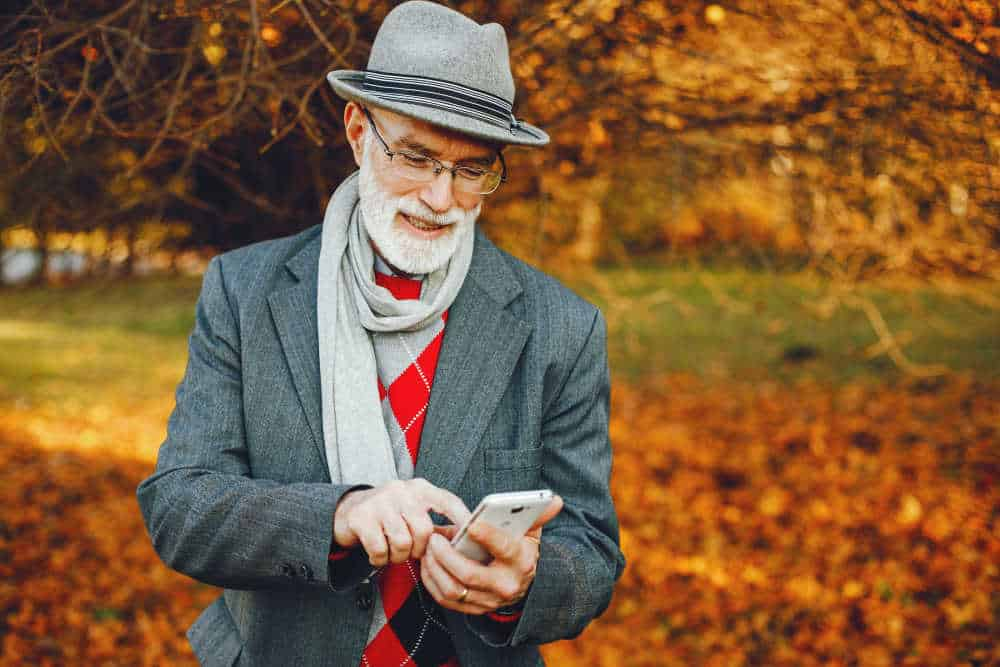 man in hat looking at phone