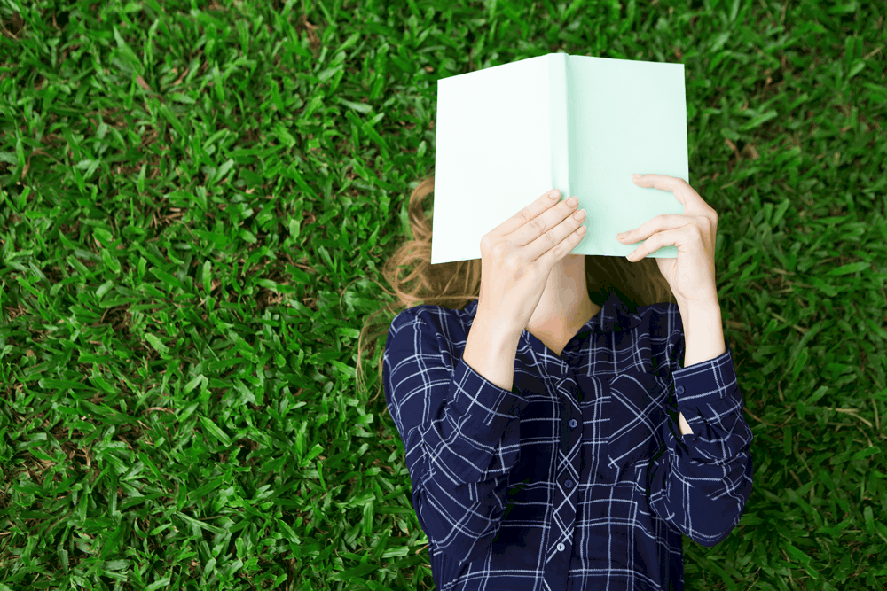 woman lying in grass reading