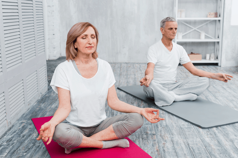 couple meditating on yoga mats