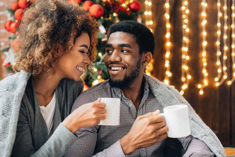 couple holding mugs near christmas tree