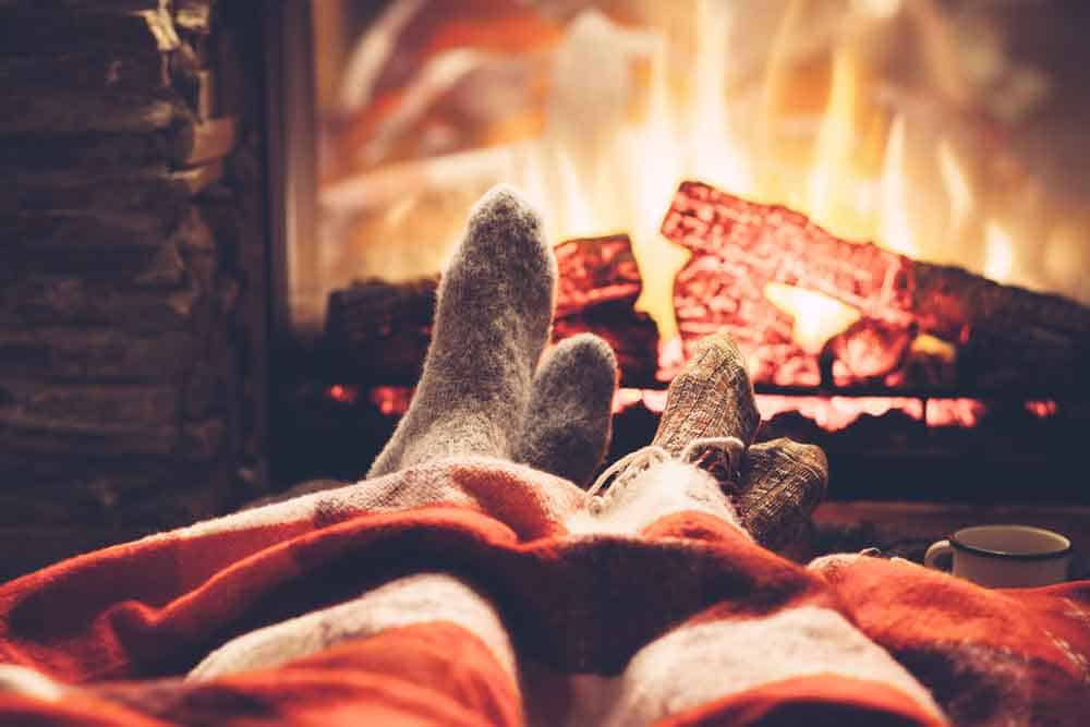 feet in socks by fireplace