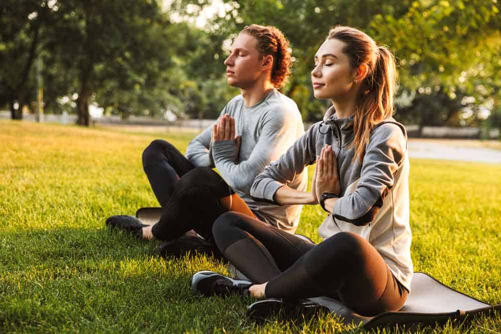man and woman meditating in park