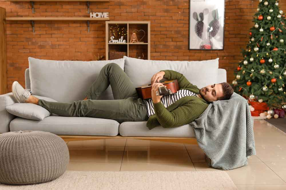 man lying on couch playing guitar
