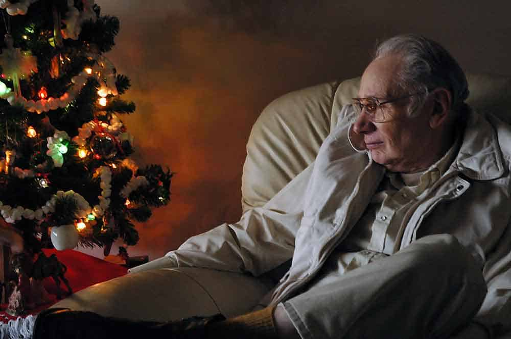 senior man looking at christmas tree