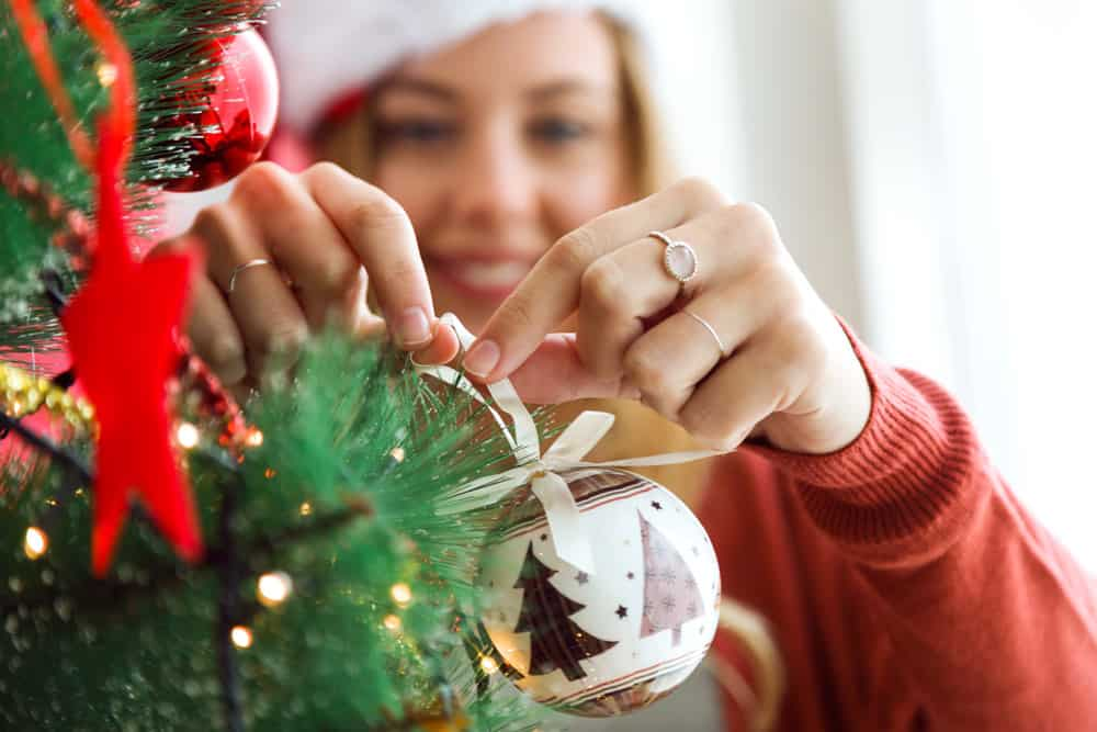 woman-decorating-christmas-tree-with-white-ball