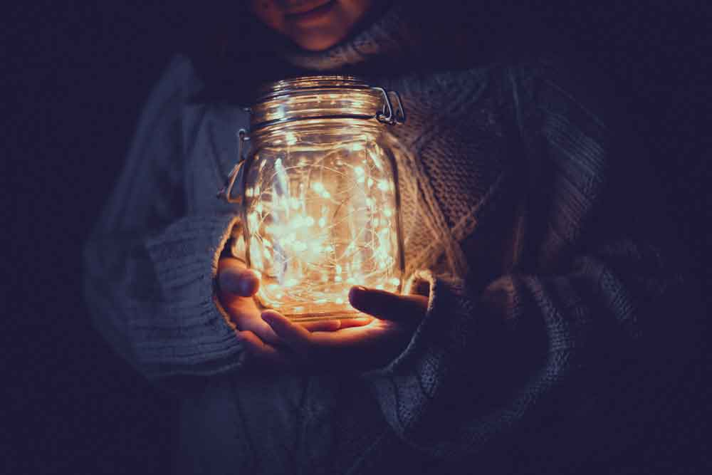 woman holding lights in a jar