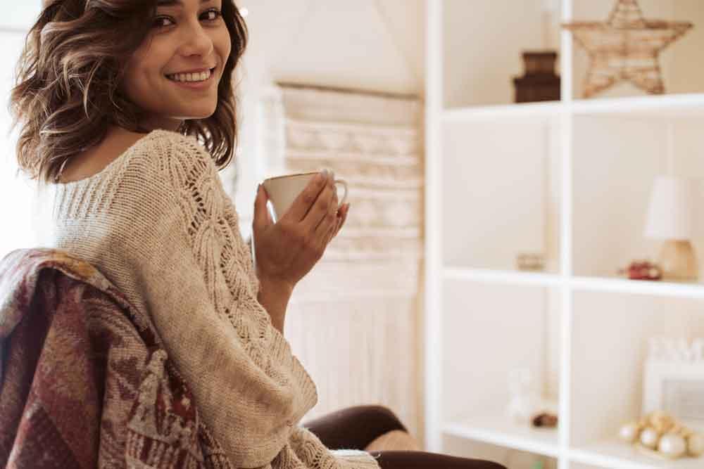 woman holding mug at desk smilin