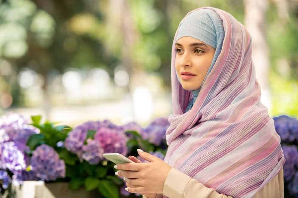 woman wearing hijab holding mobile