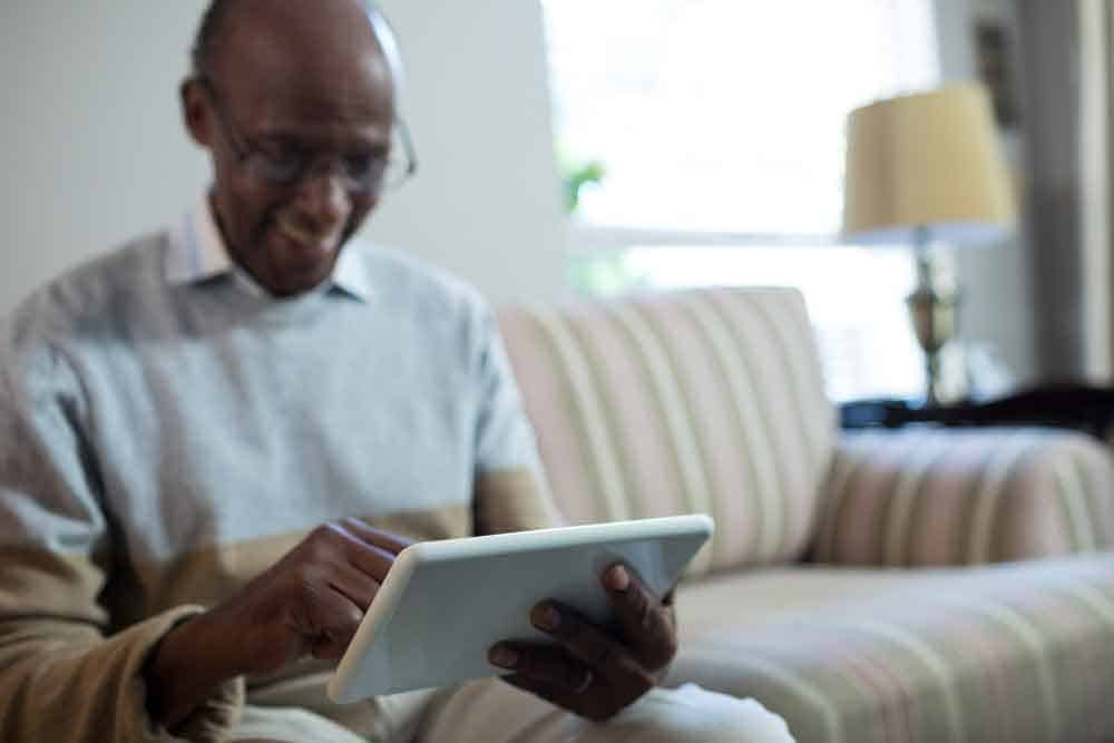 man smiling at tablet