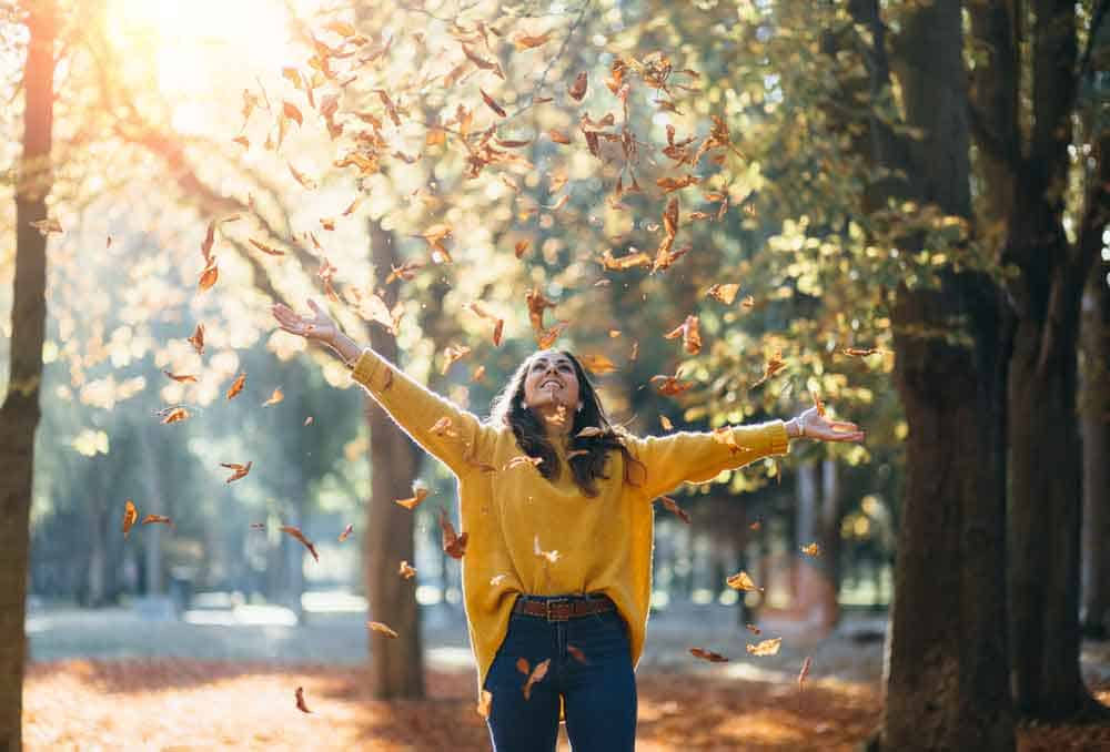 woman dancing under autumn leaves