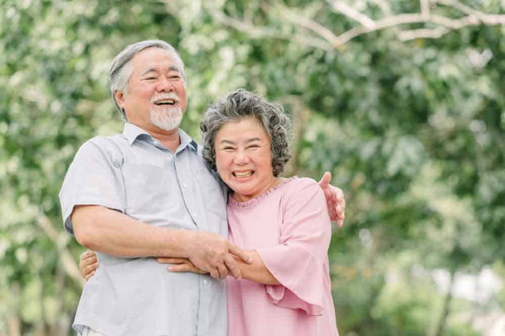 couple hugging in park smiling