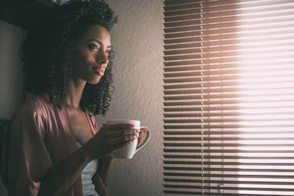 woman sitting window with cup