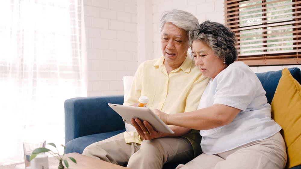 asian-elderly-couple-using-tablet-search-medicine-information-living-room-couple-using-time-together-while-lying-sofa-when-relaxed-home
