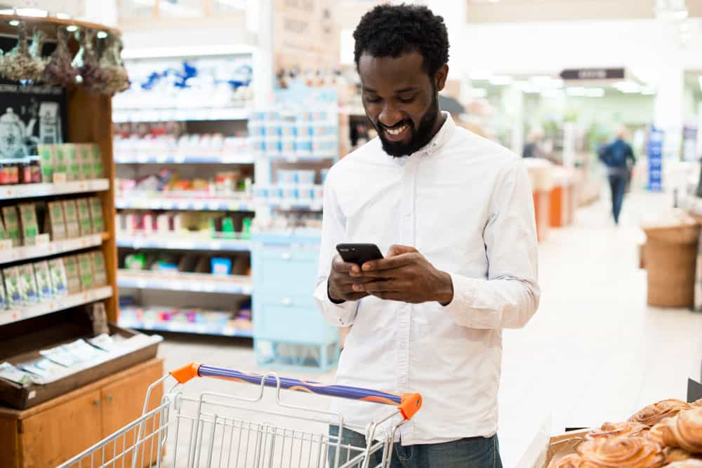 cheerful-black-man-typing-cellphone-grocery-store
