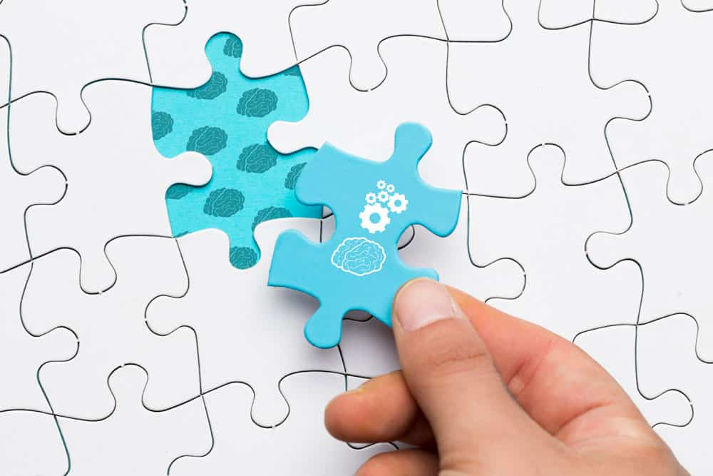 close-up-human-hand-holding-blue-puzzle-piece-with-brain-cogwheel-drawing