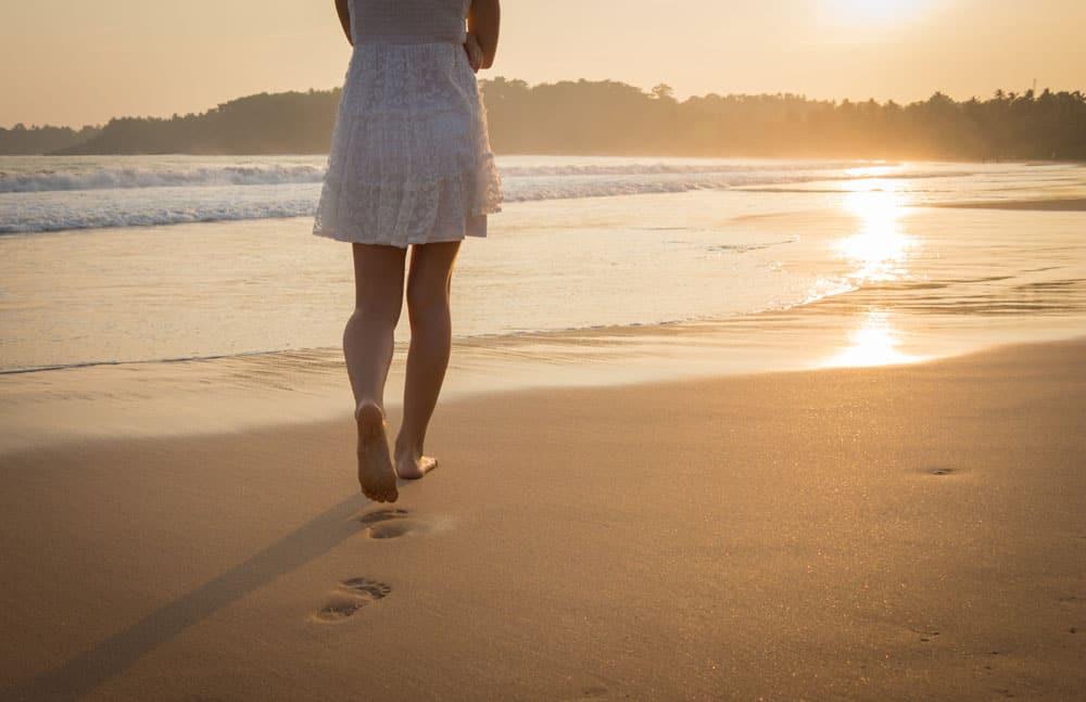 girl-white-dress-walking-along-ocean-beach-view-legs-bare-feet