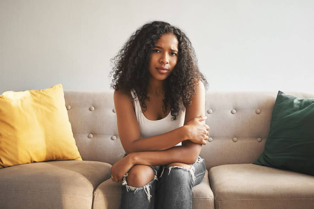 indoor-shot-beautiful-fashionable-young-mixed-race-woman-with-afro-hairstyle-sitting-couch-home-frowning-having-worried-sad