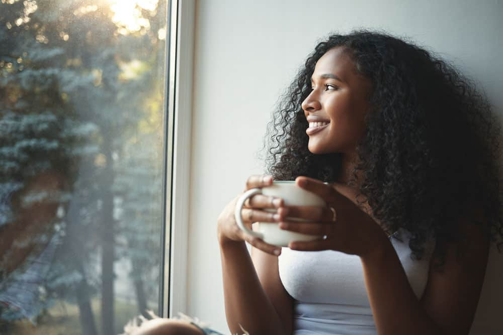 morning-routine-portrait-happy-charming-young-mixed-race-female-with-wavy-hair-enjoying-summer-view-through-window-drinking-good-coffee-sitting-windowsill-smiling-beautiful-daydreamer