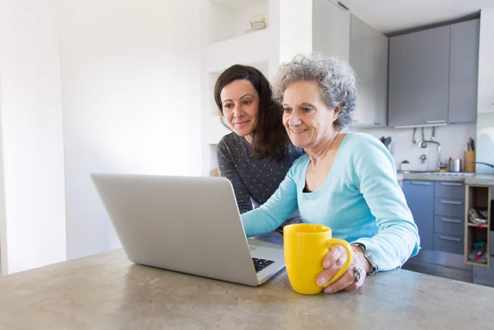 positive-senior-lady-showing-photos-daughter-laptop