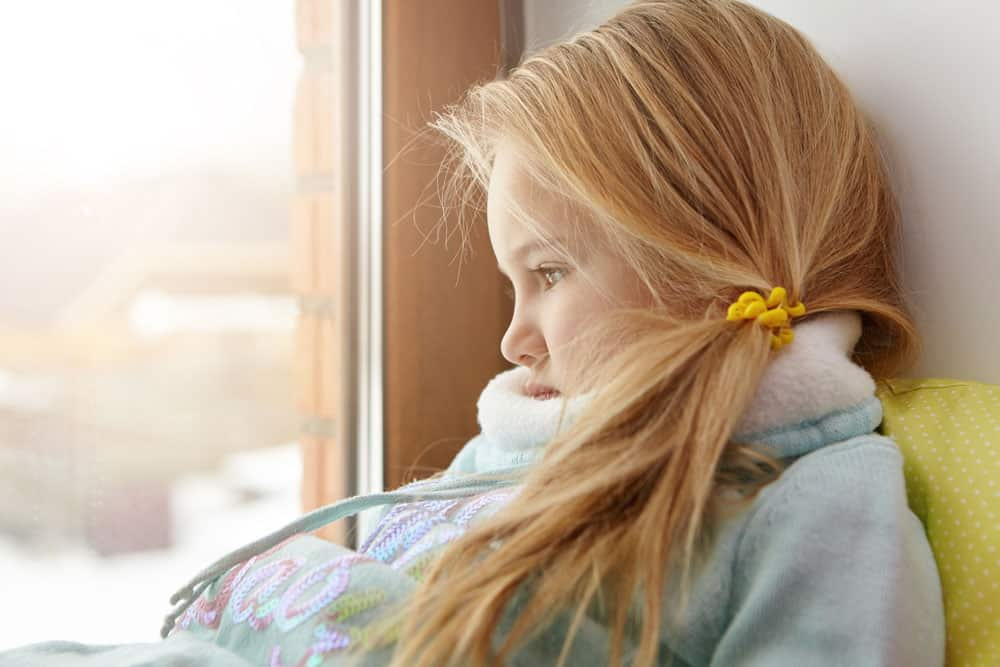 sad-cute-female-child-with-blonde-hair-sitting-windowsill