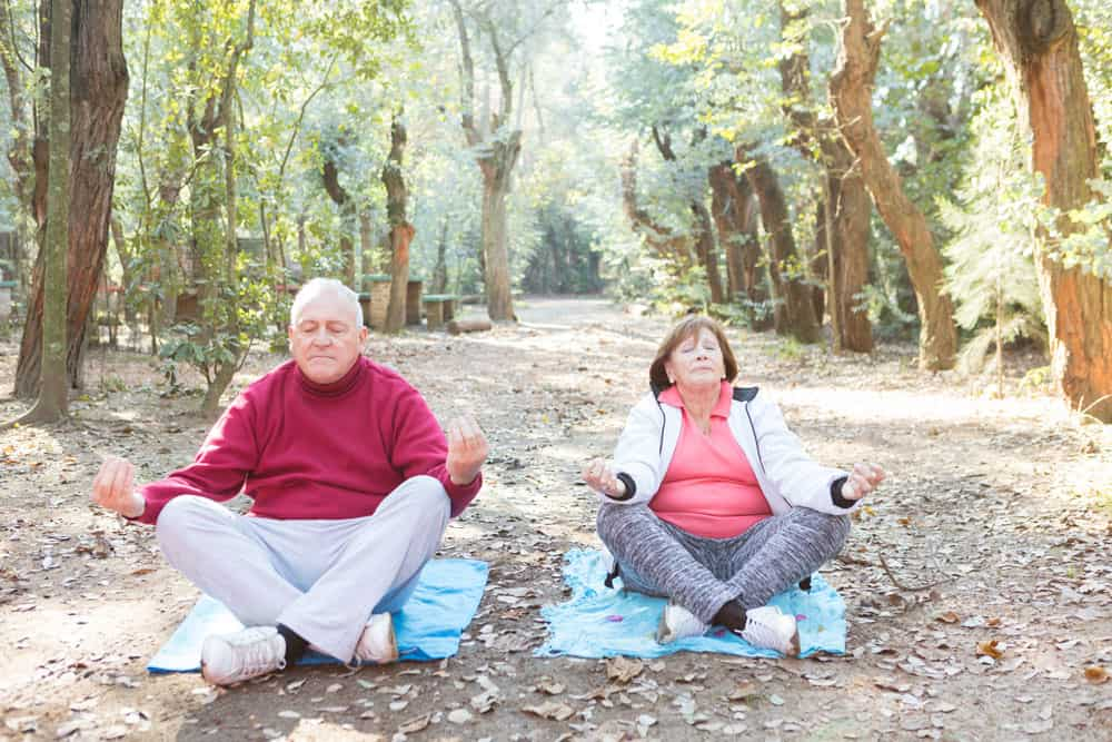 senior-couple-with-crossed-legs-during-meditation