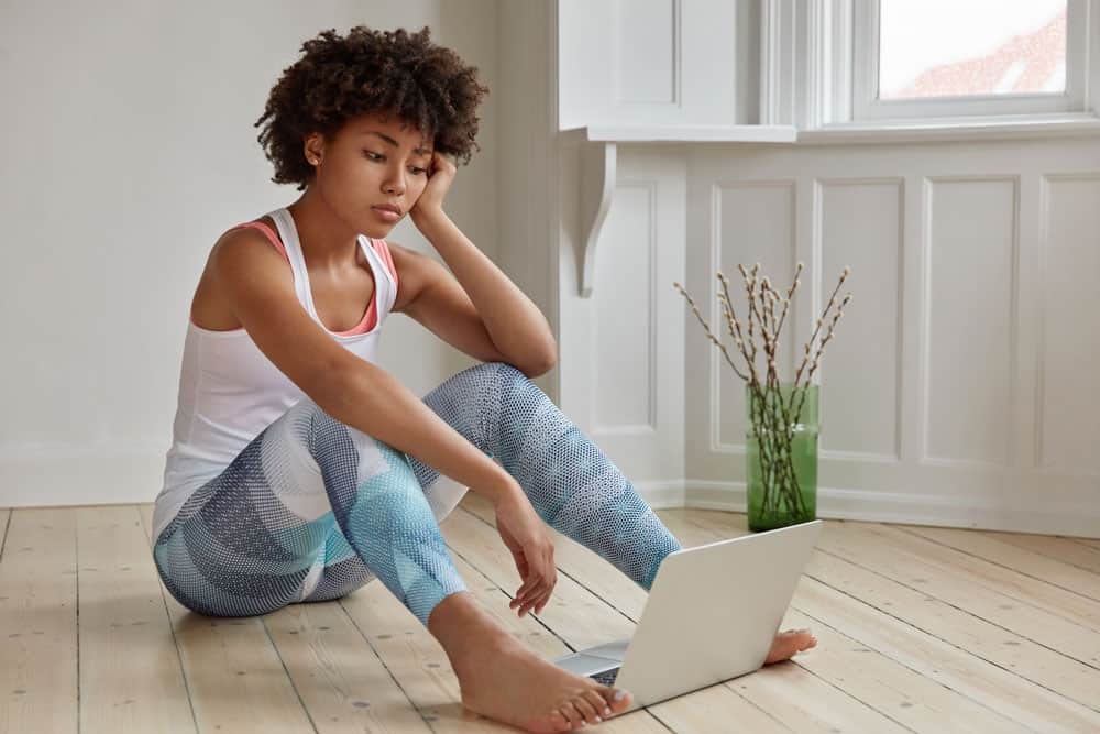 student-dressed-casual-outfit-sits-bare-foot-wooden-floor-empty-room-with-laptop-compute-1