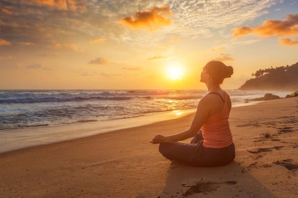 woman-doing-yoga-oudoors-beach-padmasana-lotus-pose