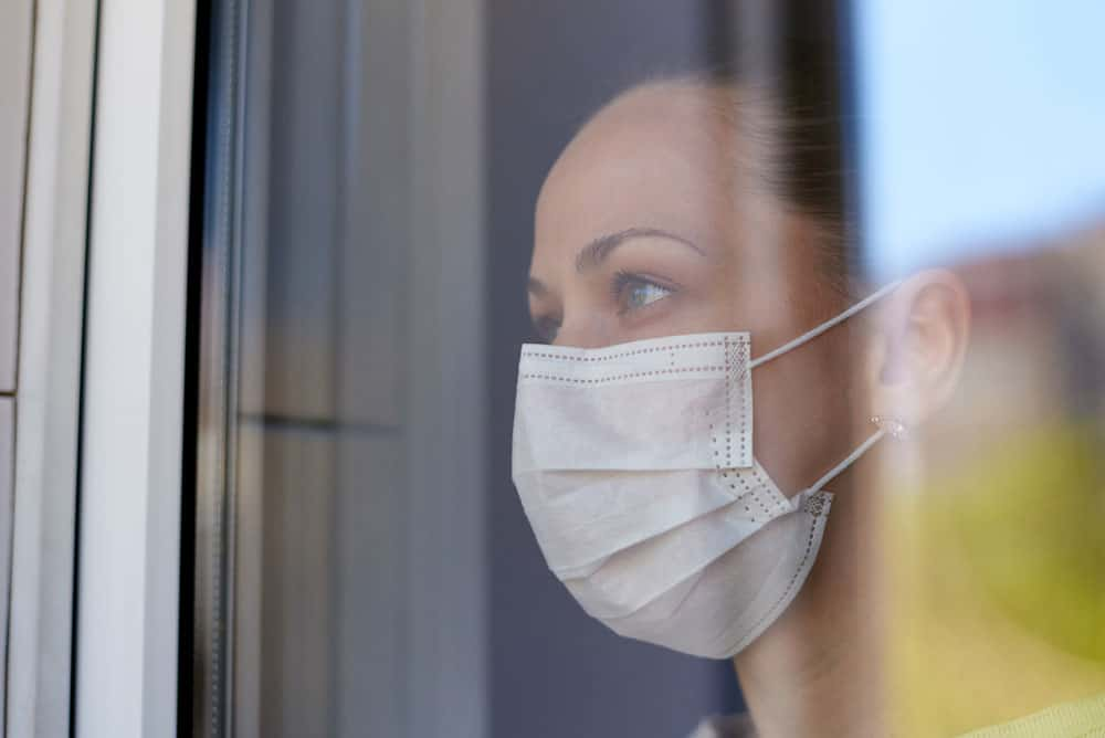 young-sad-woman-medical-mask-quarantine-looks-out-window