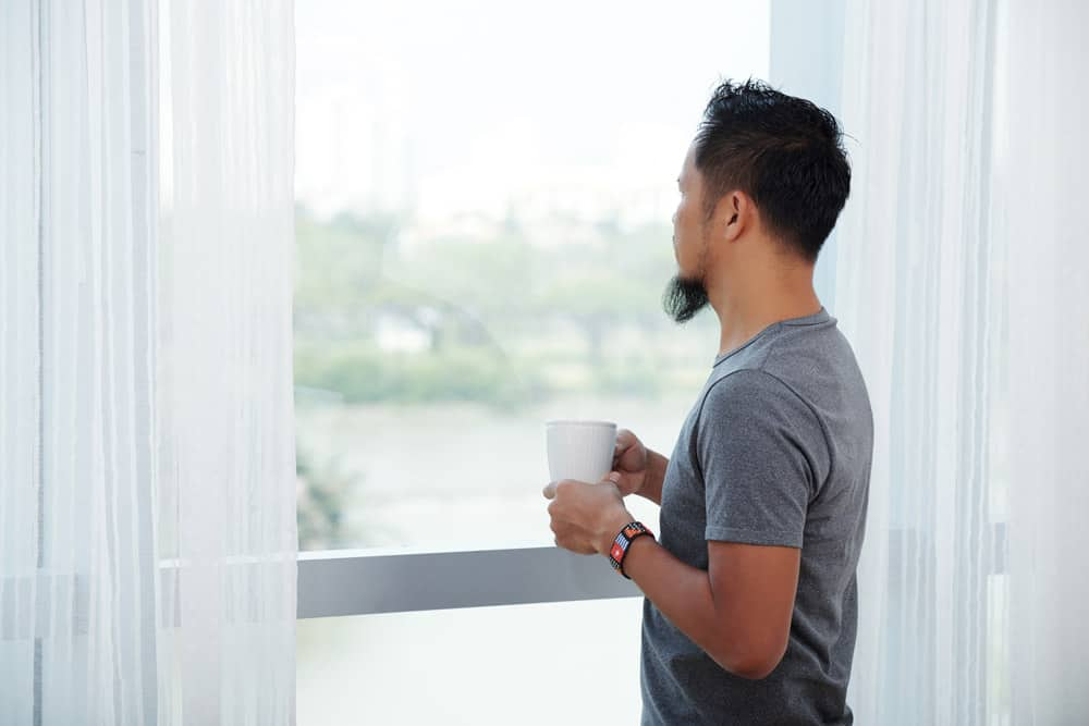 asian-man-standing-front-tall-window-with-mug-looking-out