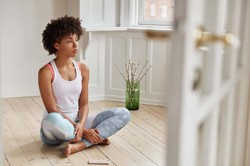 horizontal-view-contemplative-dark-skinned-woman-makes-legs-folded-dressed-casual-clothes-has-rest-after-morning-workout