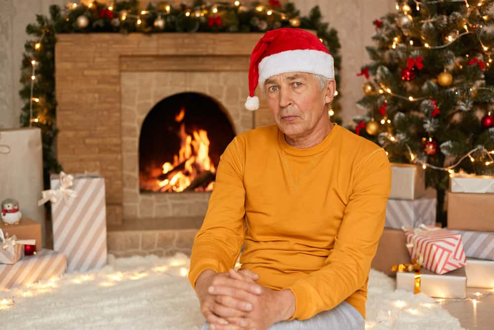 sad-senior-man-sitting-living-room-celebrating-christmas-eve-alone-has-upset-facial-expression-wearing-yellow-jumper-santa-claus-hat
