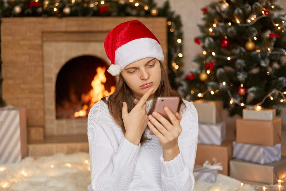 upset-female-wearing-white-sweater-santa-hat-chatting-with-somebody-woman-reads-sms-phone-being-bed-mood-keeping-finger-chin-looks-device-s-screen-with-sad-expression