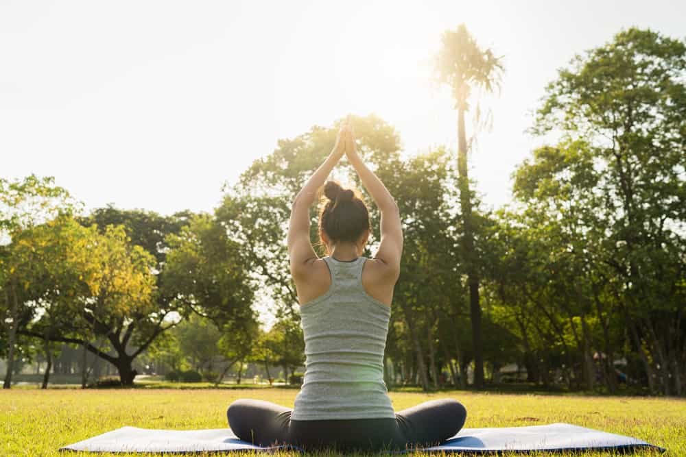 young-asian-woman-yoga-outdoors-keep-calm-meditates-while-practicing-yoga