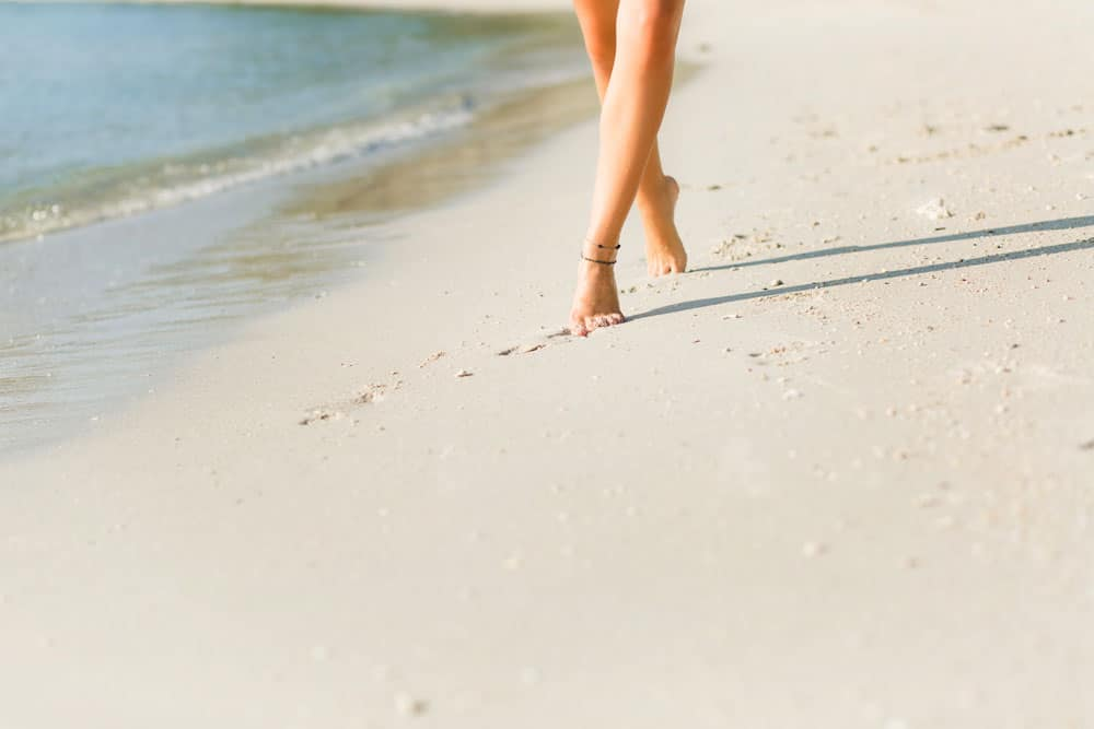 close-up-tanned-slim-girl-s-feet-sand-she-walks-near-water-sand-is-gold