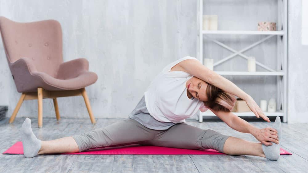 elder-woman-doing-stretching-yoga-living-room