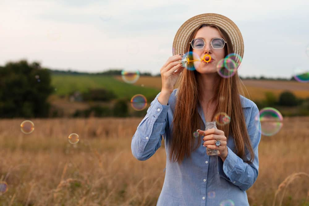 front-view-woman-blowing-bubbles-outdoors-nature