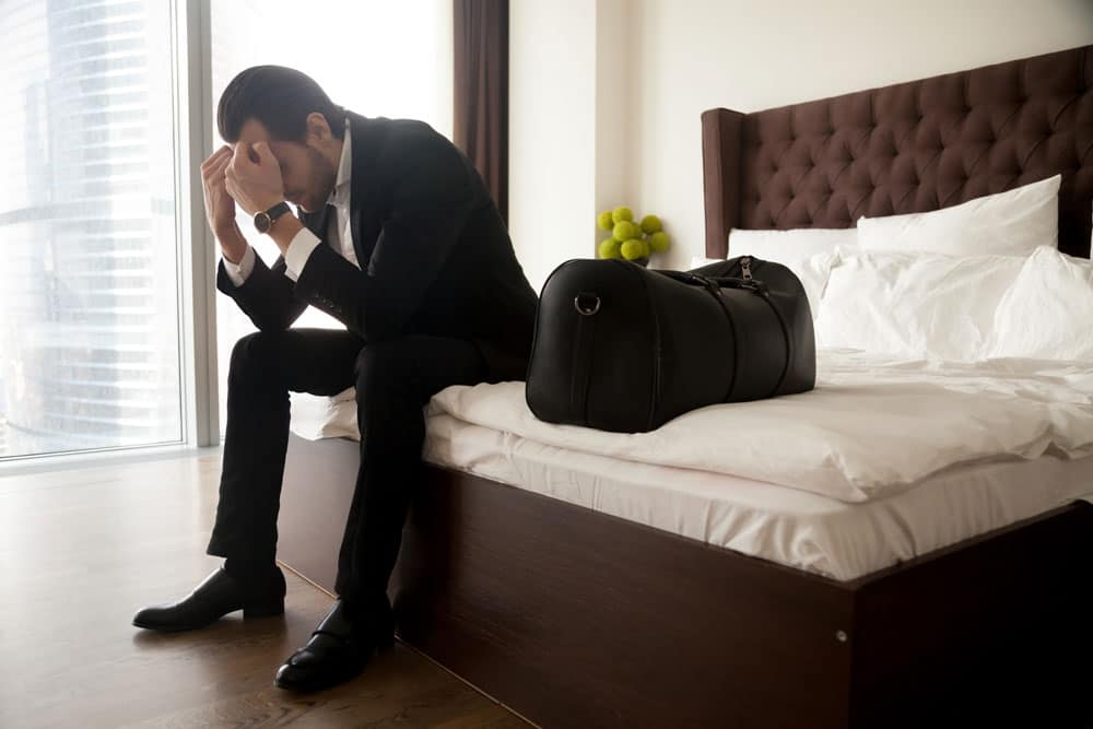 frustrated-man-suit-sitting-bed-besides-luggage-bag