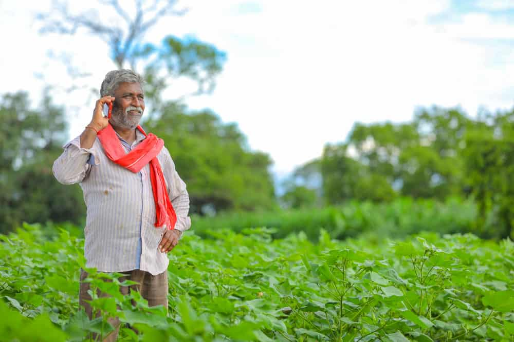 indian-farmer-talking-mobile-phone-agriculture-field