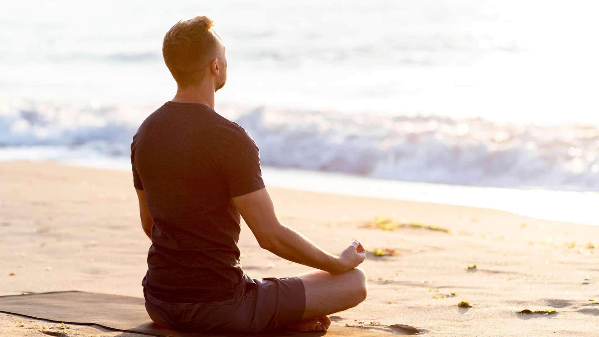 man-meditating-on-beach