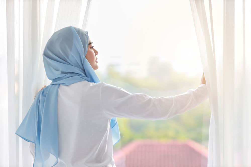 rear-view-beautiful-asian-muslim-woman-wearing-white-sleepwear-stretching-her-arms-after-getting-up-morning-sunrise-cute-young-girl-with-blue-hijab-standing-relaxing-while-looking-away
