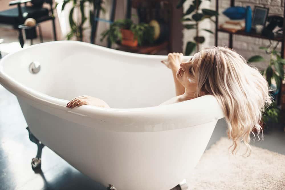 senior-caucasian-woman-posing-bathtub-with-anti-aging-cream-face