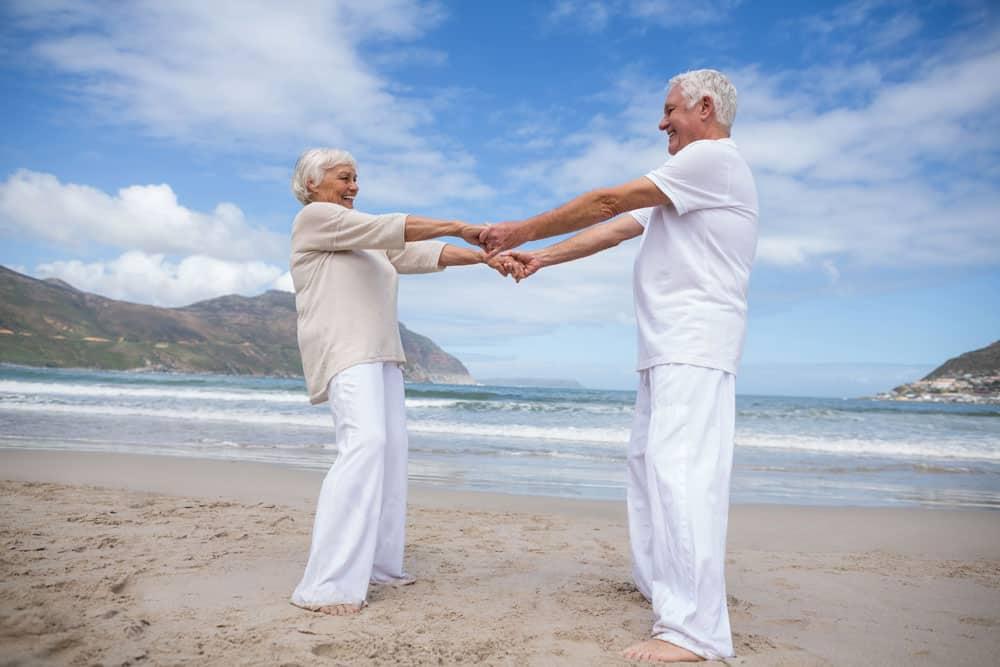 senior-couple-having-fun-together-beach