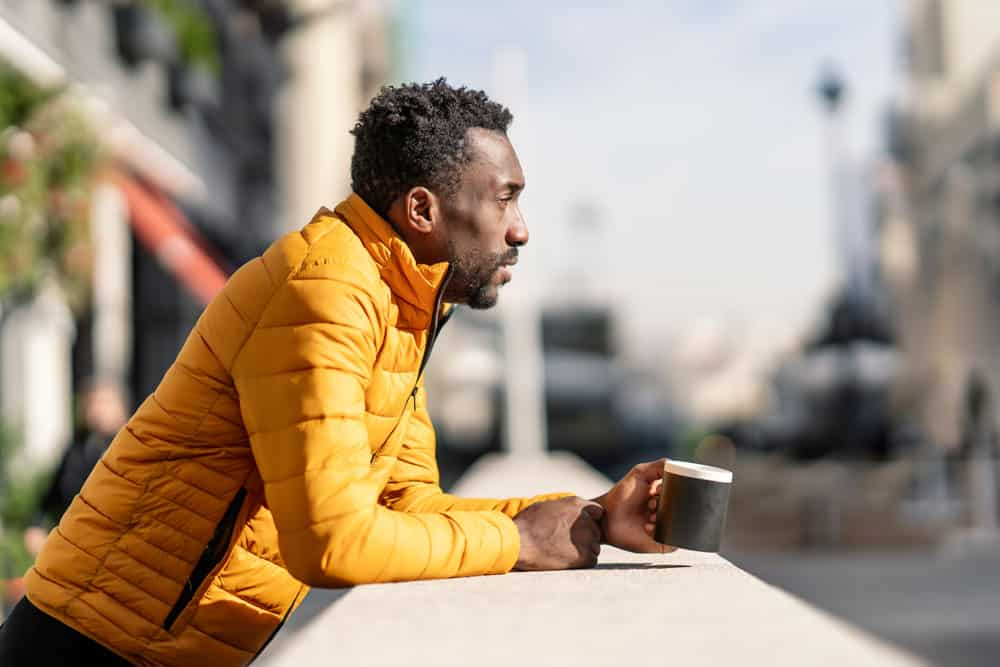 side-view-portrait-serious-african-man-leaning-balcony-holding-cup-coffee-contemplating-views-city