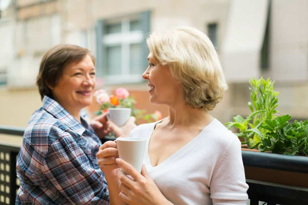 two-mature-housewives-drinking-tea-terrace