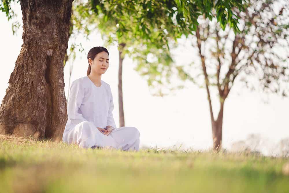 young-asian-woman-relaxes-wearing-white-dress-meditation-green-grass-fields