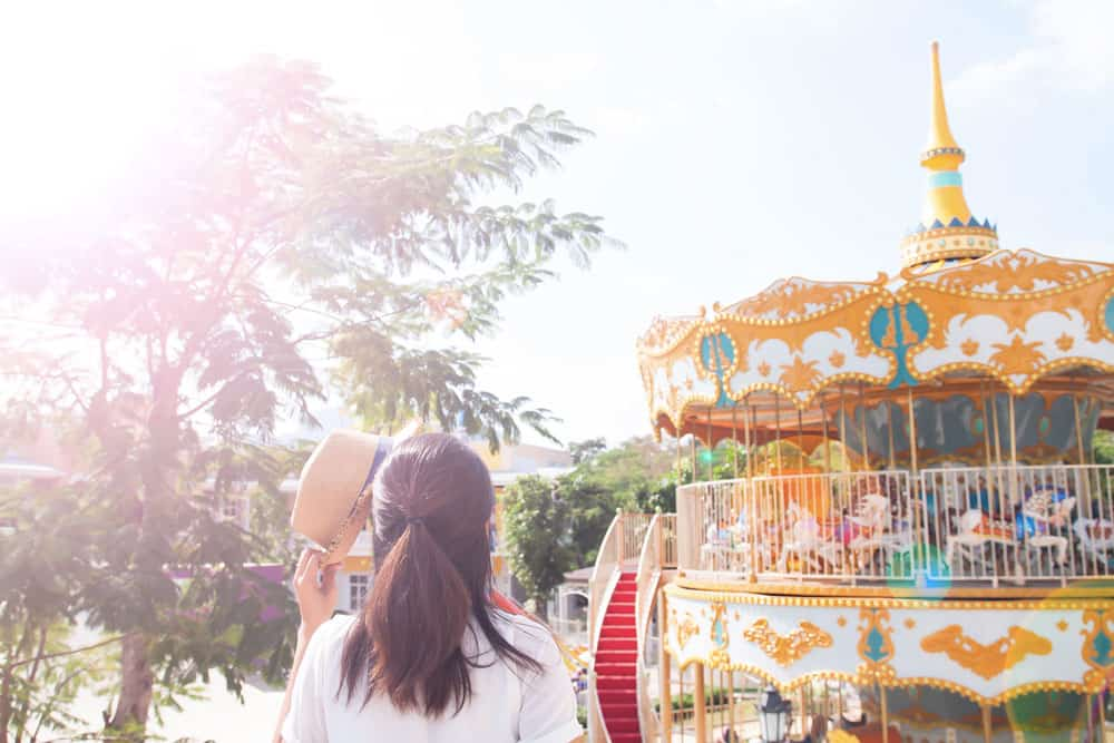 young-woman-holding-hat-sunny-day-with-amusement-park-ride-background
