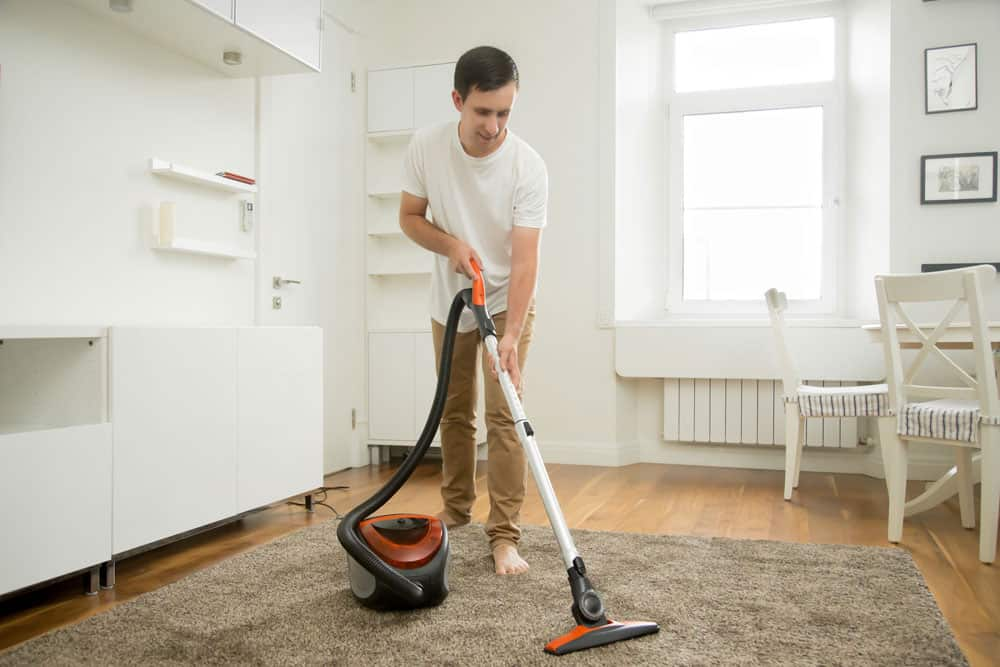 happy-smiling-man-cleaning-carpet