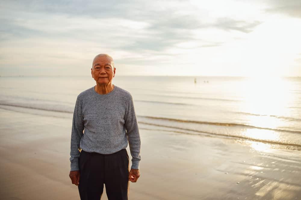 asian-senior-old-man-practice-tai-chi-yoga-pose-beach-sunrise